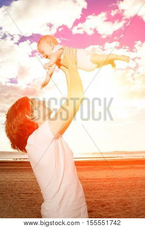 Happy father throws up baby boy against blue sky and white clouds