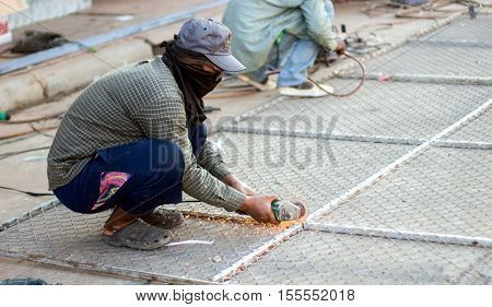 asian man cutting steel net cage with electrict saw with no safty