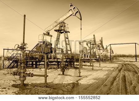 Group of oil pumps and wellheads in the oilfield during winter. Oil and gas concept. Toned.