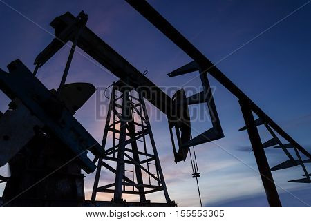 Oil pump and pipeline silhouette during sunset at the oilfield. Oil and gas concept.