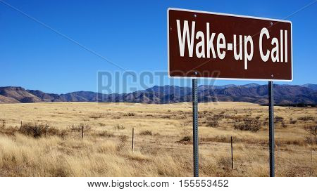 Wake up Call road sign with blue sky and wilderness