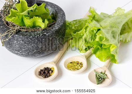 spices for cooking and fresh salad with pounder on white background close up