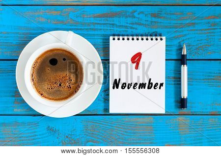 November 9th. Day 9 of month, coffee or hot chocolate cup with calendar on designer workplace background. Autumn time, top view.