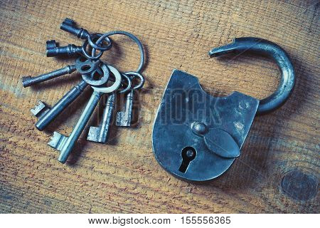 Old padlock and a bunch of keys on a wooden board