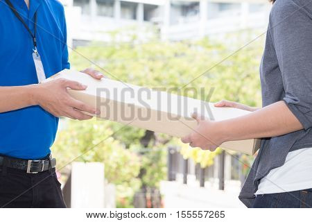 Woman hand accepting a delivery of boxes from deliveryman