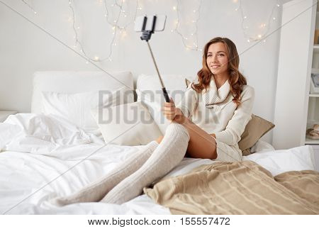 technology, christmas, winter and people concept - happy young woman in bed taking picture by smartphone selfie stick at home bedroom