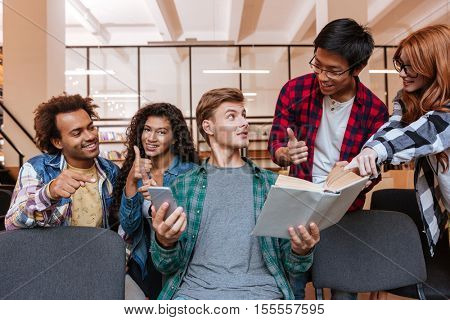 Smiling young man with cell phone and book sitting and talking with his friends