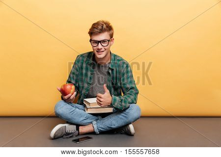 Smiling handsome young man in glasses with book and apple showing thumbs up over yellow background