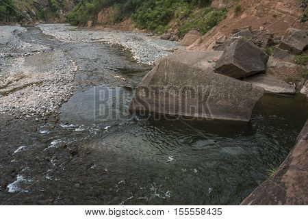 Mountain river with a big rock in the middle of the water