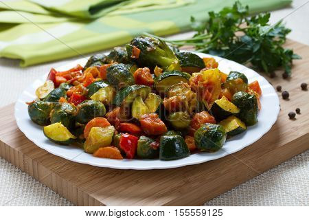 Fried vegetables on white plate with herbs and pepper on wooden desk