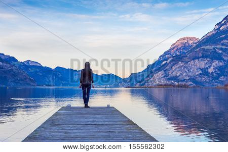 Epic landscape complete with a small woman figure. Mountain lake and sky in bright colors of sunset