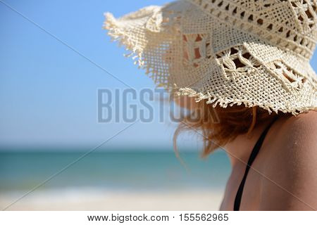 Relaxing Woman Enjoying The Summer Sun Relaxing Standing With A Sun Hat At The Beach. Enjoy Her Free