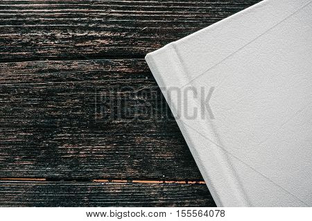 Hard cover on white leather book. Details on dark brown wood