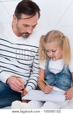 For better understanding. Handsome attractive intelligent man holding a pencil and looking at the copybook while explaining something to his daughter