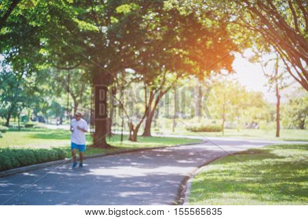 Blurry scene of man jogging inside public park in morning. Park surrounded by green tree and sunlight shine through gap of tree from bright sky.