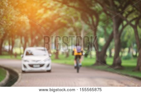 Blurry scene of biker cycling bicycle passed small white car in public park with soft sunlight.