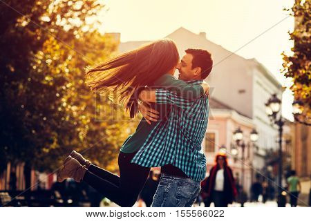 Handsome man holding his girlfriend in the arms