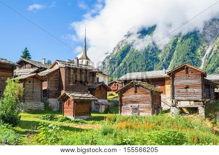 Sun-burnt chalets green forests and meadows in Valais tradition swiss Alps village Blatten