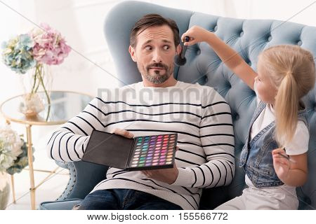 Mums cosmetics. Cheerful nice pretty girl sitting on the sofa and holding a make up brush while playing with cosmetics of her mum