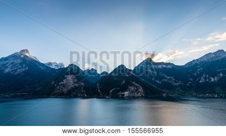 Evening in the Alps. Rays of of the setting sun over the mountain peaks. Lake Uri. Mountainous landscape wide lens.