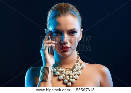 Closeup glamour fashion portrait of beautiful stylish Caucasian young woman model with bright makeup, with red lips and fashionable necklace with blue backlit