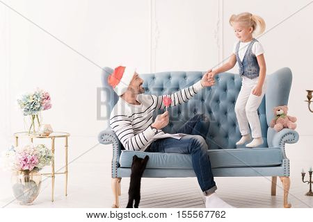 Constant support. Nice pleasant loving father wearing a Santa hat and looking at his daughter while holding her hand
