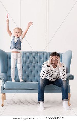 Problems with upbringing. Pensive sad depressed father holding his head and looking at you while having some problems with his daughter upbringing