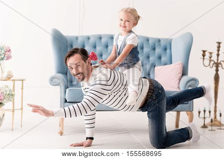 Being with family. Happy funny optimistic man being on all fours and grabbling while having fun with his child