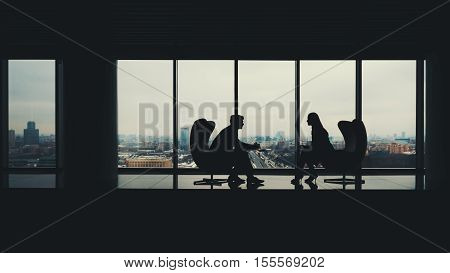 Silhouettes of two business people man and woman sitting on armchairs in office interior man showing information on screen of his laptop to his colleague huge windows with winter cityscape outside