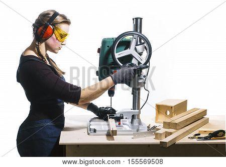 beautiful female carpenter at work using vertical drilling machine. Photo on white background.