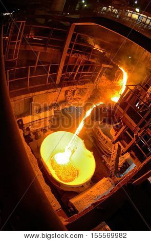 Hot steel pouring in ladle car train in steel plant