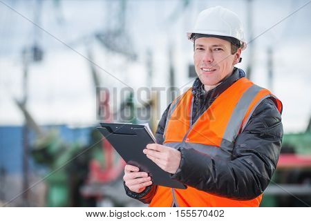 handsome electrical engineer holding papers in substation