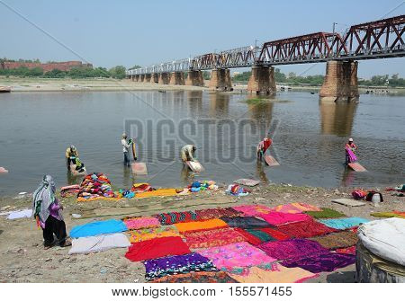 People Washing And Drying Cloth On River