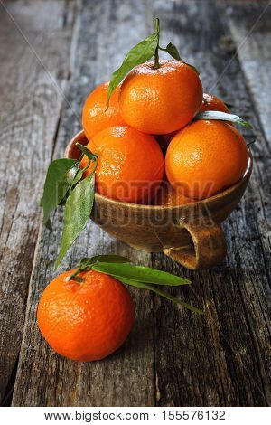 Tangerines with green leaves on old wooden table
