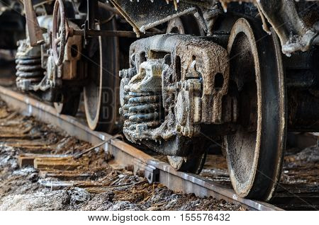 Train rusty wheels covered by salt of Baskunchak lake, Russia. It is salt stains on surface of railroad carriage. Train are ready to carry another load of salt produced there. Close-up shot.