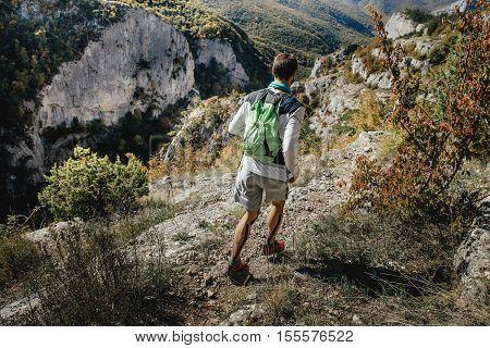 athlete male runner running along edge of a cliff during mountain marathon