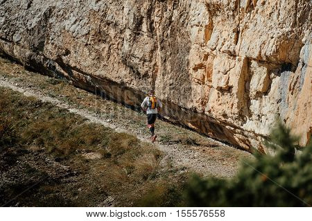 male runner running on a track along steep cliff during mountain marathon