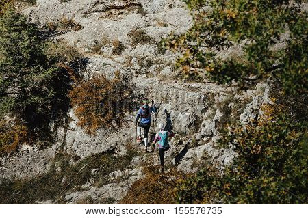 athletes runners man and woman climb a mountain with walking poles