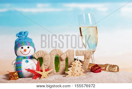Figures 2017, a bottle of champagne and glass, snowman, Christmas tree, starfish, Christmas gifts in the sand against the sea.