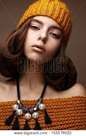 Beautiful girl in a knitted hat on her head and a necklace of pearls around her neck. The model with gentle make-up and gold lips. Beautiful face. Photo taken in a studio. Gentle and cozy winter look.