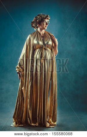 Pregnant woman in golden toga and wreath posing like a Greece fertility goddess Demetra