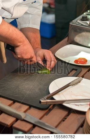 Image Of Male Chef With Knife Cutting Vegs
