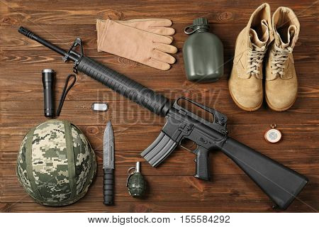 Set of military outfit on wooden background, top view