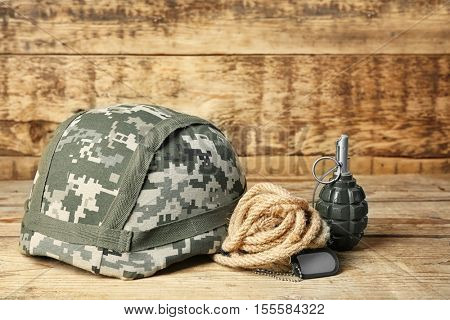 Military helmet, grenade and dog tag on wooden background, close up