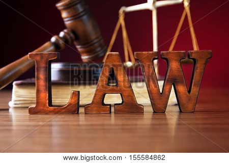 Law concept. Justice scales, judges gavel and book on wooden table and red background