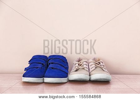 Different baby shoes on light wall background