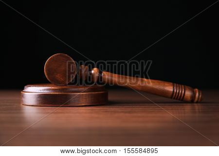 Judges gavel on wooden table and black background