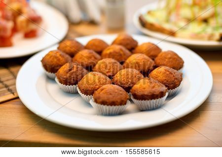 Some Appetizing Plain Muffins In A White Ceramic Plate On A Set Table