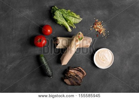 Doner kebab - fried beef meat with vegetables in tortilla on the black chalkboard