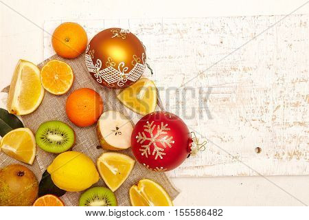 Christmas food concept - tropical fruits citrus fruits with Christmas decorations top view copy space